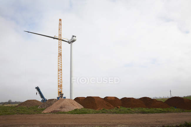 Wind turbine erecting with crane in industrial landscape — Stock Photo
