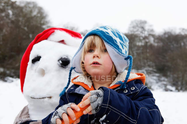 A boy with a carrot for a snowmans nose — Stock Photo