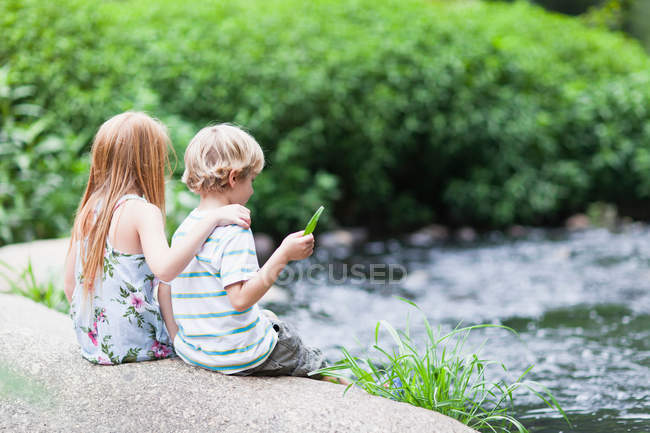 Children sitting on rock together — Stock Photo