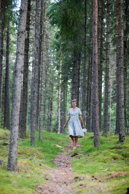 Woman walking on path in forest — Stock Photo