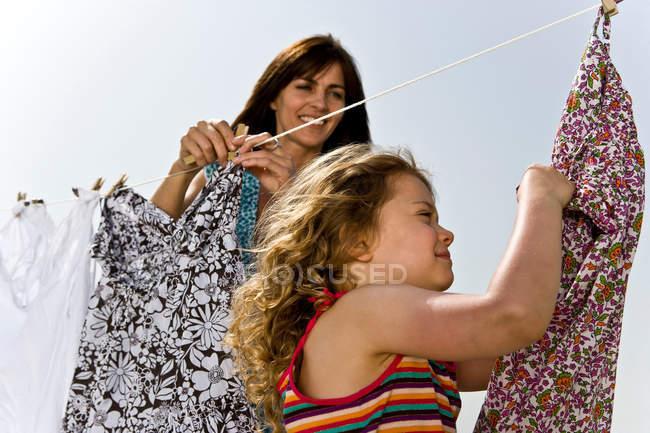 Дівчина з матір'ю підвішування одягу — стокове фото