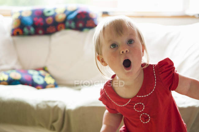 Toddler girl gasping in living room — Stock Photo