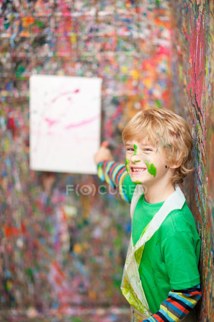 Boy pointing to painting on paint-splattered wall — Stock Photo