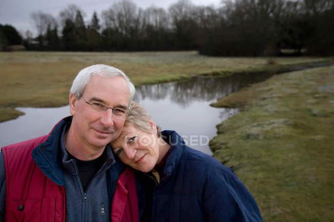 Pares aposentados que sorriem na câmera ao ar livre — Fotografia de Stock