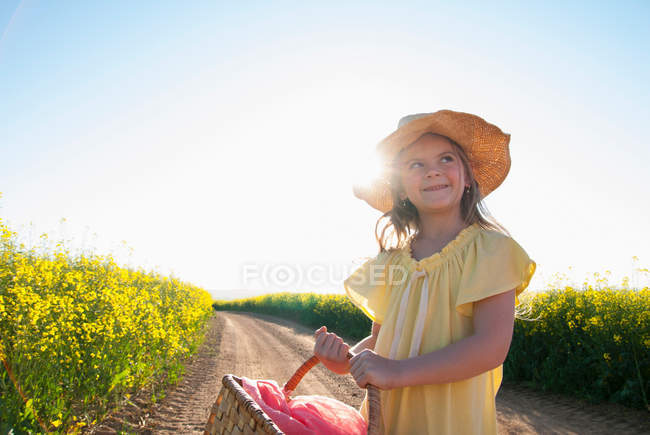 Girl carrying basket on dirt road — Stock Photo