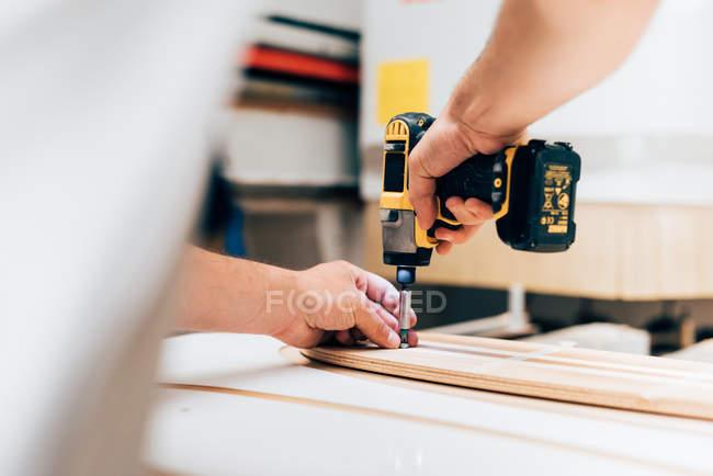 Vista recortada del joven en taller de carpintería con destornillador inalámbrico, atornillado en madera contrachapada - foto de stock