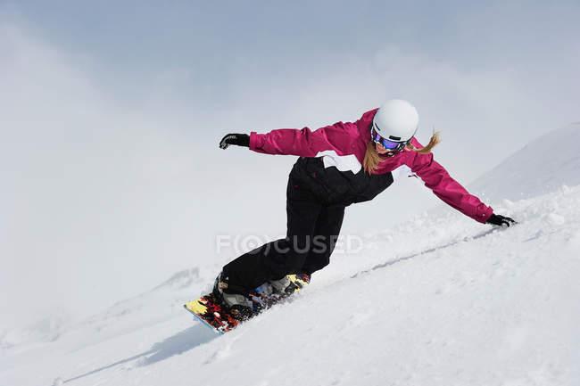 Молодая женщина, сноуборд вниз по склону — стоковое фото