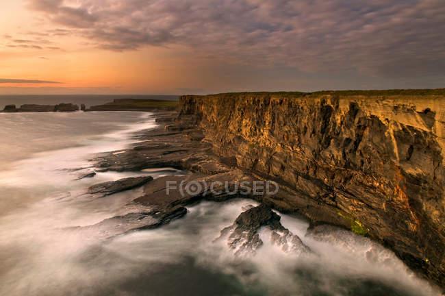 Fog rolling up to rocky coastal cliffs — Stock Photo
