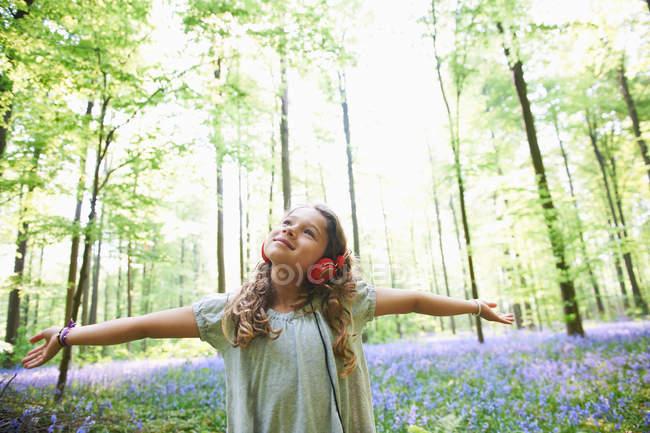 Девочка слушает музыку в наушниках в лесу — стоковое фото