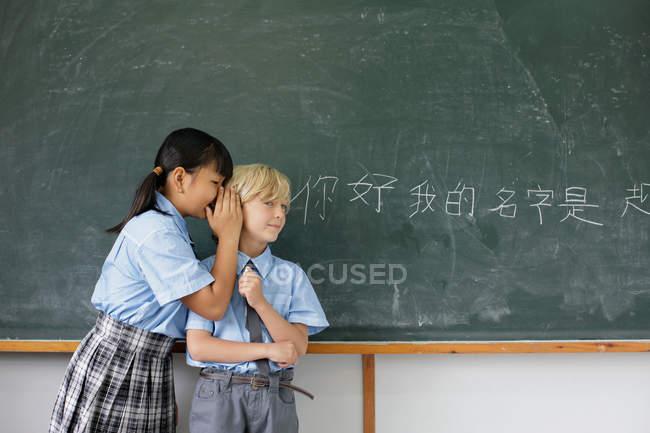 Crianças em idade escolar compartilhando respostas — Fotografia de Stock