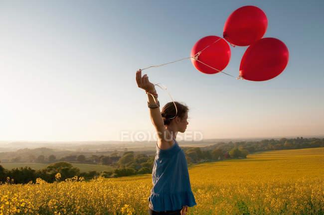 Fille portant des ballons dans le champ — Photo de stock