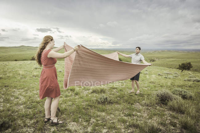 Young couple on hilltop folding pink blanket, Cody, Wyoming, USA — Stock Photo