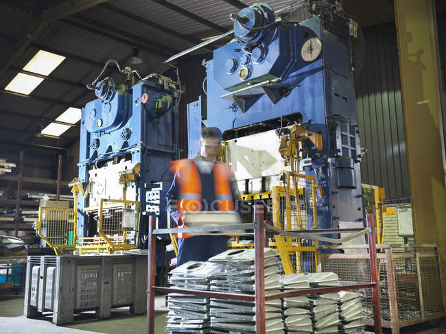 Arbeiter mit Metallpresse in Blechfabrik — Stockfoto