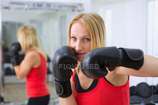 Boxer training with gloves in gym — Stock Photo