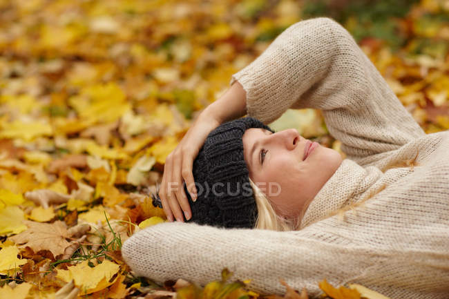 Woman laying in autumn leaves outdoors — Stock Photo