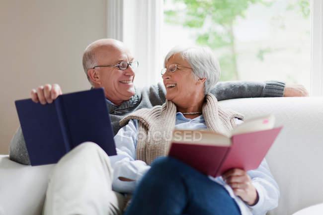 Lächelndes älteres Paar liest Bücher — Stockfoto