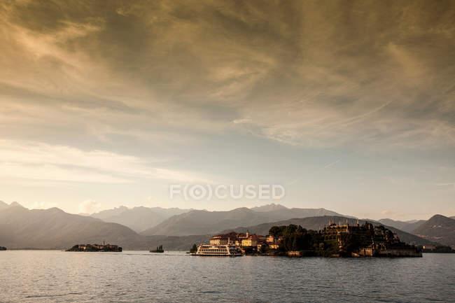 Montanhas sobre vila rural e lago — Fotografia de Stock