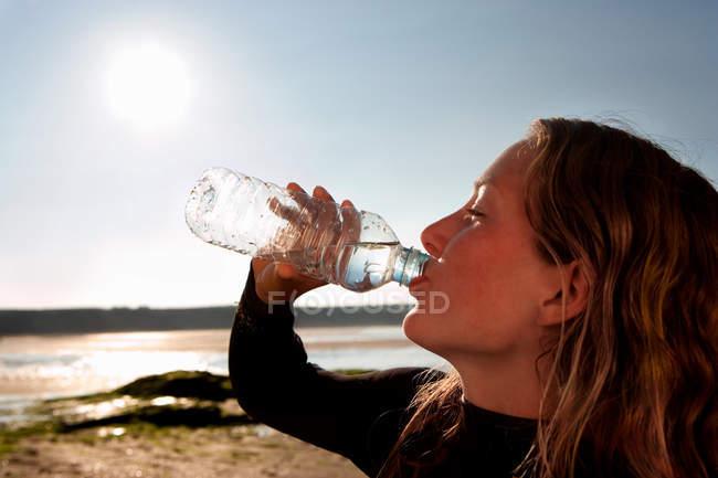 Femme eau potable en combinaison — Photo de stock
