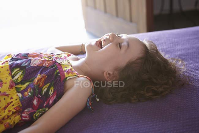 Ragazza sdraiata sul letto e ridendo — Foto stock