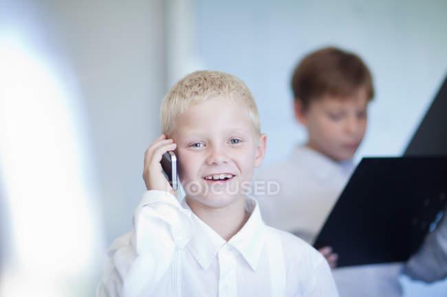 Улыбающийся мальчик с мобильного телефона — стоковое фото