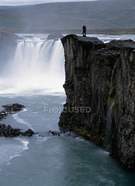 Любуясь скал туристы и водопад — стоковое фото