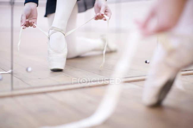 Ballerina putting on ballet slippers — Stock Photo