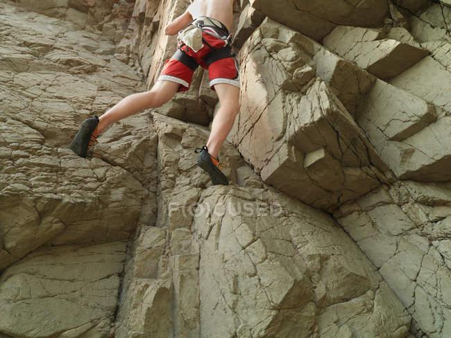 Rock climber scaling steep rock face — Stock Photo