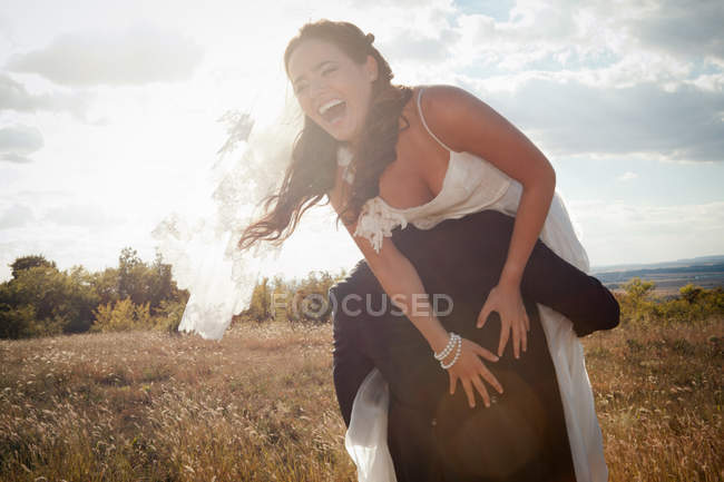 Newlywed groom carrying bride outdoors — Stock Photo