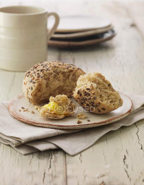 Rotolo di pane ai semi misti con burro — Foto stock