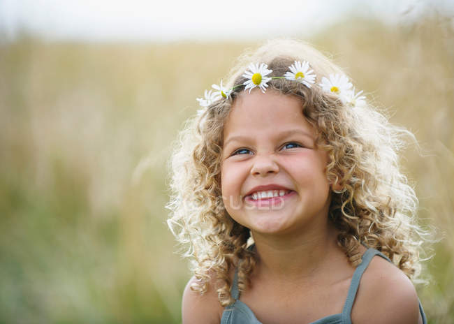 Young girl laughing with daisies in hair — Stock Photo