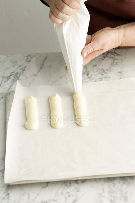 Female hands piping dough on sheet — Stock Photo