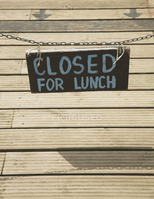 Closed for lunch sign hanging over decking — Stock Photo