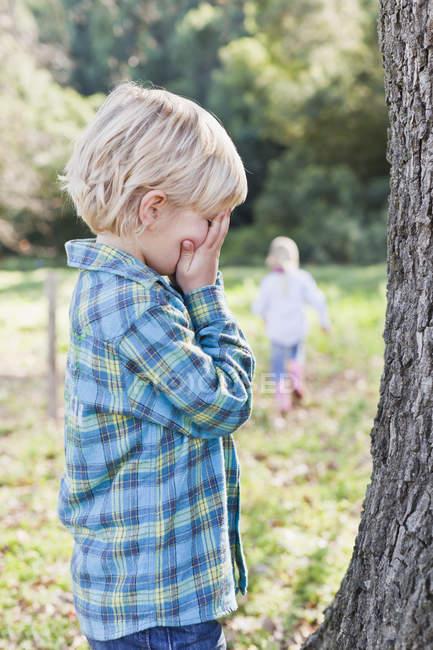 Crianças brincando esconder e procurar ao ar livre — Fotografia de Stock
