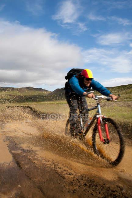Hombre montando bicicleta de montaña en barro - foto de stock