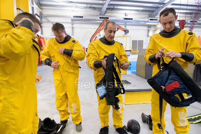 Offshore oil workers putting on diving equipment in training pool facility — Stock Photo