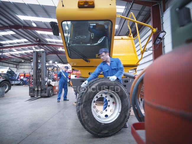 Ingénieurs se préparant à réparer la roue dans l'usine de réparation de camions — Photo de stock