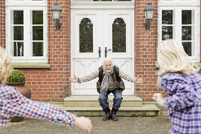 Grandfather welcoming grandchildren with arms open — Stock Photo
