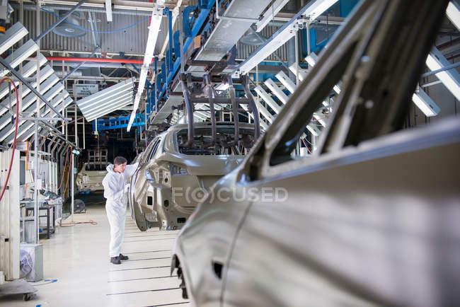 Працівник оглядають кузова автомобіля у автомобільного заводу — стокове фото