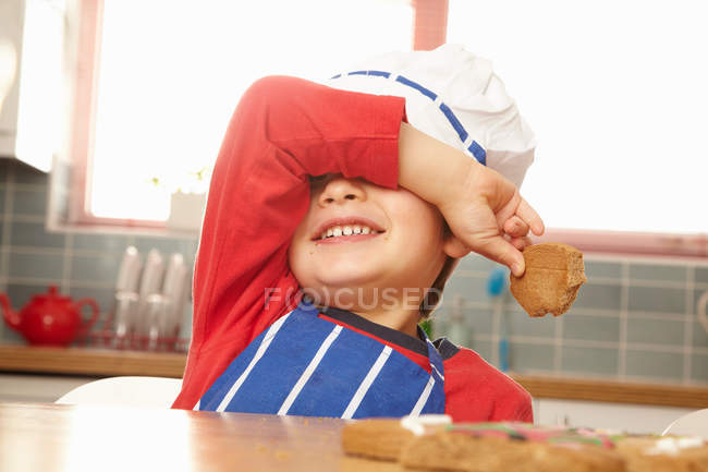 Мальчик ест печенье в кухне — стоковое фото