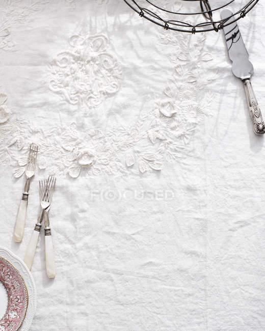 Besteck auf traditionelle weiße Tischdecke — Stockfoto