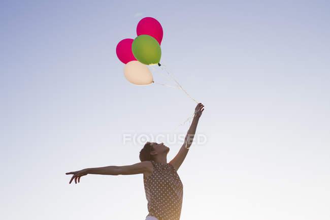 Vista basso angolo di donna matura tenendo su mazzo di palloncini contro il cielo blu — Foto stock