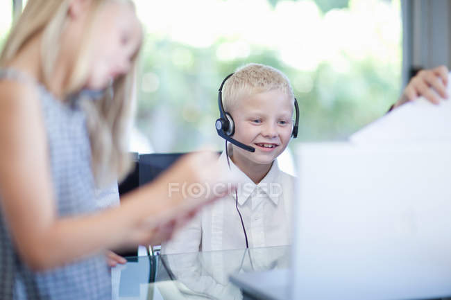 Smiling boy in headset on background of children — Stock Photo