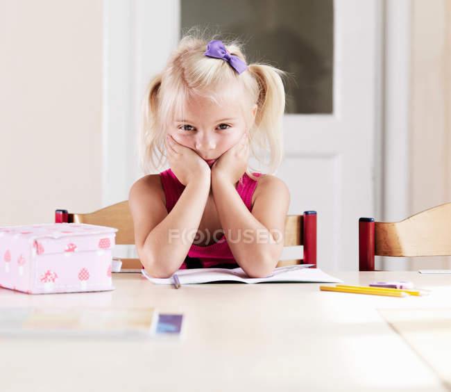 Bored girl doing homework at table — Stock Photo