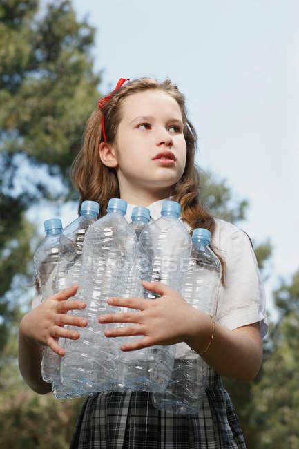 Girl holding empty bottles — Stock Photo