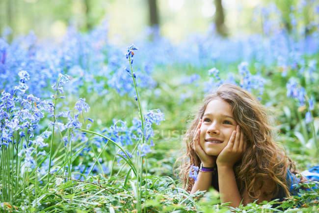 Девушка, лежащая в поле цветов — стоковое фото