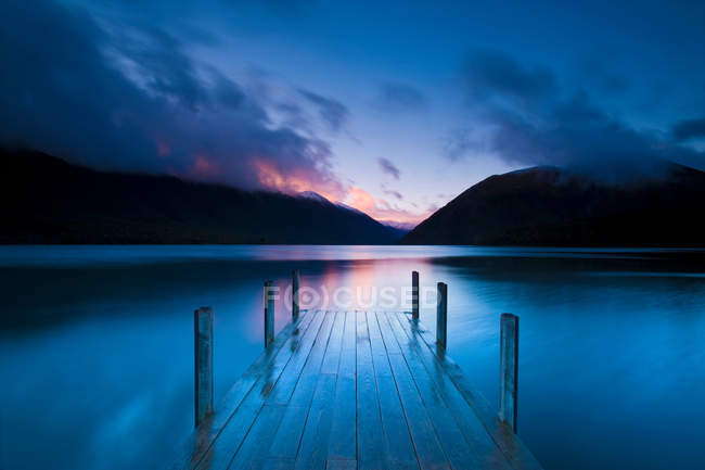 Wooden pier stretching into still lake — Stock Photo