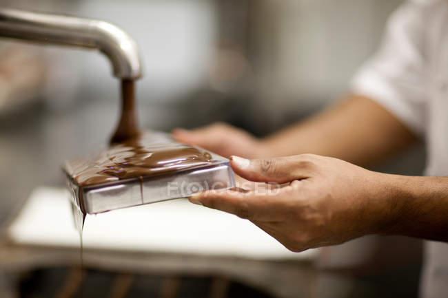 Людина, що заповнення форми розплавленим шоколадом — стокове фото