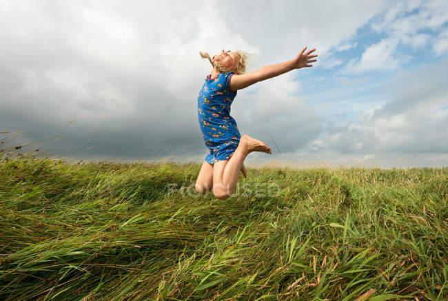 Девушка прыгает в поле высокой травы — стоковое фото