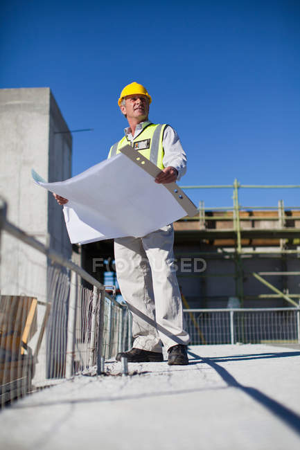 Worker reading blueprints on site — Stock Photo