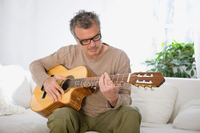 Man strumming guitar at home — Stock Photo